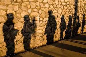 Shadows on the stone wall cast by random people